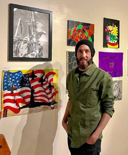 Nathan Hanford, a case worker and artist-in-residence for Soldier On, poses near veterans' artwork at Salmon Falls Gallery. Hanford teaches art classes in Pittsfield and Northampton to help veterans in transition from homelessness to permanent housing. RECORDER Staff/DIANE BRONCACCIO